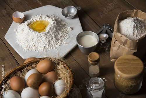 In de dag Bakkerij Bakery ingredients : flour, eggs, butter, sugar and rolling pin on vintage wood table, Sweet baking concept