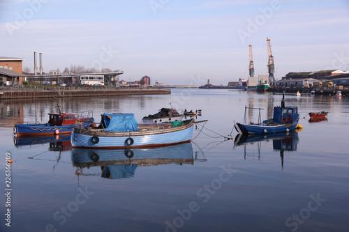 Plakat Małe łodzie rybackie w Port of Sunderland na rzece Wear rzucają swoje odbicie na spokojne wody
