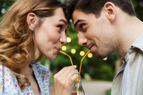 Young loving couple outdoors in park having fun drinking soda together.