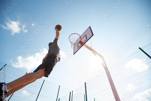 Wide angle portrait of young sportsman shooting slam dunk in basketball court outdoors, copy space