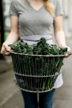 Woman Holding A Basket Of Tuscan Kale