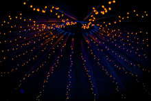 A Collection Of Small Little Orange Lights On The Top Of A Purple Ceiling Of A Tent At A Wedding At Night In The UK
