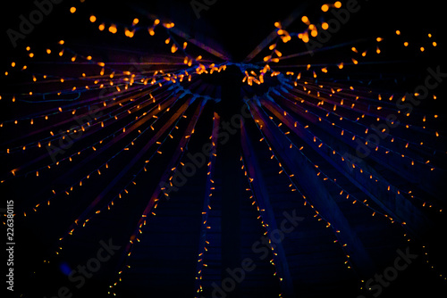 Photo A collection of small little orange lights on the top of a purple ceiling of a t