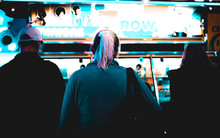A Group Of Tourists Spend Money Inside A Dark Neon Blue Arcade Playing On A Penny Machine