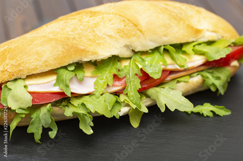Baguette sandwich with ham, tomatoes, cheese and arugula lettuce. Delicious Breakfast or snack. Close up