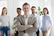 Smiling millennial confident businessman stands with arms crossed looking at camera with happy cheerful business partners team on background. Successful teamwork, company owner and leadership concept