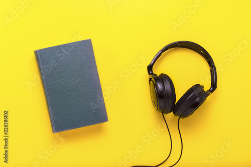 Valokuvatapetti Book with a blue cover with text English and black headphones on a yellow background