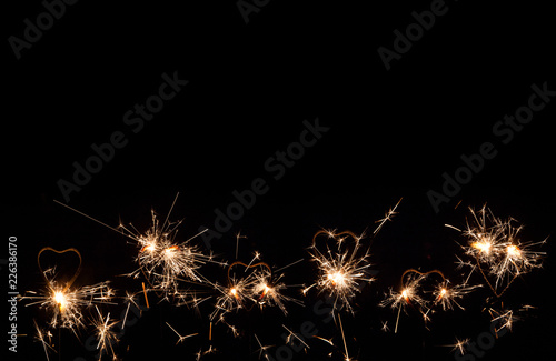 a lot of heart shape burning sparklers isolated on black background birthday party background