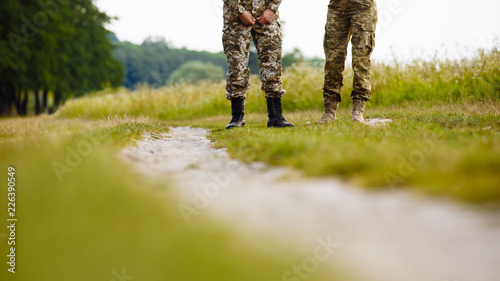 Fotografía  view of the legs of two men in military uniforms in boots near the pathway in the field on the background of nature