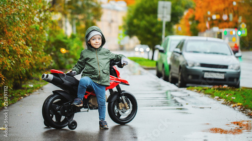 Fotomural A beautiful little boy posing at his children's red motorcycle
