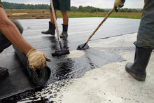 Roofer Worker Painting Bitumen Praimer At Concrete Surface By The Roller Brush Waterproofing