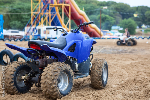 All-terrain vehicle (ATV) is on sandy beach for rent or driving for fun, cross-country tires