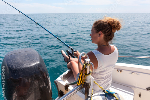 Young woman has angling excursion, sitting in boat with spinning rod