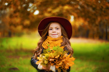 Portrait Of A Smiling Young Girl Who Is Holding In Her Hand A Bouquet Of Autumn Maple Leaves In The Park