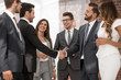 smiling business people shaking hands with each other