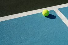 Tennis Ball Rests On Blue Tenn...