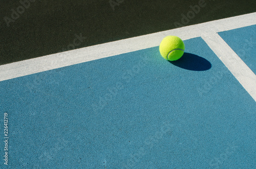Leinwand Poster Tennis ball rests on blue tennis court