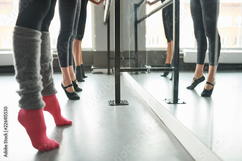Photo  Low section view at row of elegant young women practicing ballet moves standing