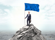 Handsome Businessman On The Top Of The Mountain With Blue Flag
