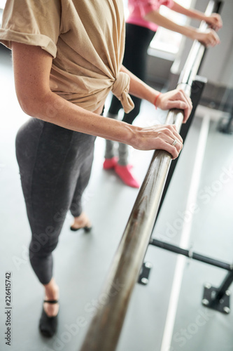 High angle view at unrecognizable young woman practicing ballet standing at bar Canvas Print