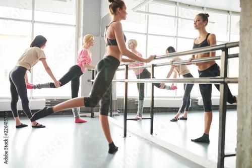 Photo  Full length portrait of female ballet teacher positioning students in dance clas
