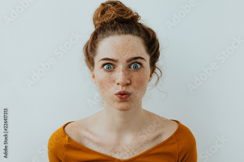 Woman portrait. Style. Beautiful blue eyed girl with freckles is pouting lips at camera, on a white background