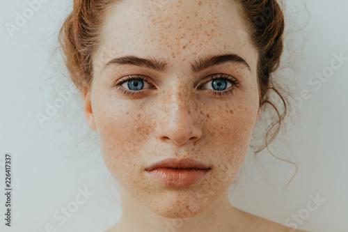 Fototapeta premium Portret kobiety. Zbliżenie. Piękna błękitnooka dziewczyna z piegami jest przyglądającym kamerą, na białym tle