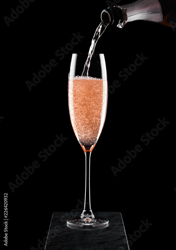 Pouring pink rose champagne from bottle to glass on black marble board on black background. Space for text