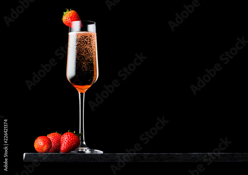 Elegant glass of pink rose champagne with strawberry on top and fresh berries on black marble board on black background. Space for text