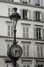 Clock And Streetlight Old And Typical Of Paris In Montmartre With A French Flag At A Window