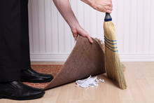 Unrecognizable Man Sweeping Dirt Under A Rug