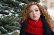 Girl with red hair in fur coat and red knitted scarf walks outdoors in winter. She stands of spruce in snow. Woman is smiling.