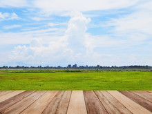 Wooden Table Top Over Green Grass Field And Blue Sky