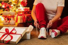 Woman In Pajamas Ties The Laces Of Athletic Shoes. Christmas Present. Birthday Present.
