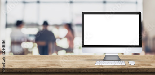 Fotomural  Blank screen desktop computer on wooden table top with blur people working at creative office bokeh background,Mock up for display or montage of design