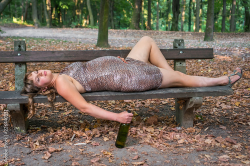Fotografering  Pregnant woman drinking wine in the park - alcoholism concept