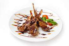 Plate Of Roasted Lamb Chops Served With Vegetables And Sauce Isolated At White Background.