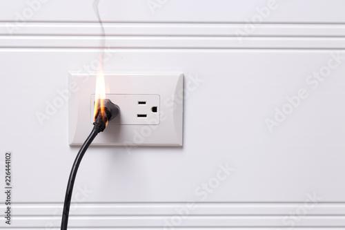 Valokuva  Overheated electric plug got on fire