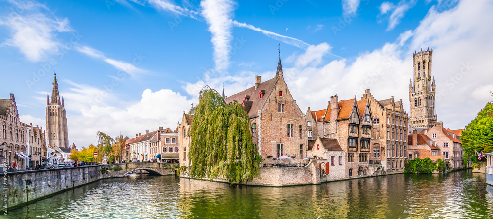 Fototapeta Panoramic city view with historical houses, church, Belfry tower and famous canal in Bruges, Belgium.