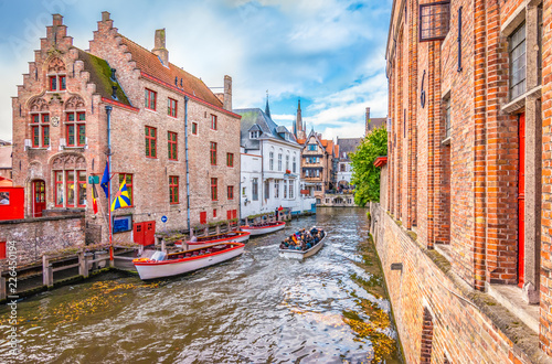 Wall Murals Bridges Boat trip on canal of Bruges. Popular for tourists who visit Belgium.