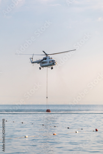 Tuinposter Helicopter A helicopter of the fire service with a fire fighting bucket is taking part in putting out a fire. A helicopter with a red basket is lowered over the sea to catch water.