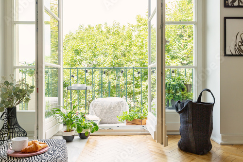 Photo Open glass door from a living room interior into a city garden on a sunny balcon