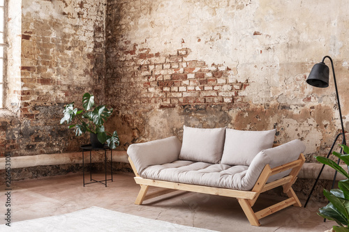 Grey sofa between plant and black lamp in wabi sabi loft interior with red brick wall. Real photo
