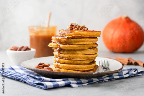 Stack of pumpkin pancakes with caramel sauce and pecan nuts on a plate, closeup view. Tasty autumn comfort food
