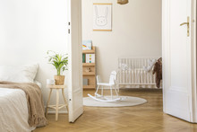 Plant On Stool Next To Bed In White Bedroom Interior With Rocking Horse On Rug And Cradle. Real Photo