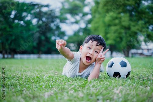 Fotografia, Obraz Little Asian child playing football and celebrating on grass.