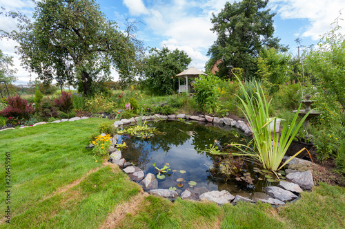 Foto auf Leinwand Garten Beautiful designed garden fish pond with water-lily in a well cared backyard gardening background