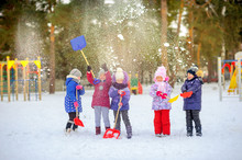 Children Play In The Winter Park, Throw Snow And Have Fun