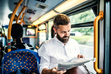 Hipster Man On A Bus In The City, Travelling To Work And Reading Newspapers.