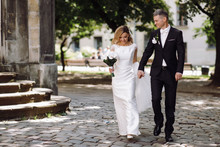 Groom Holds Bride's Hands Tender Walking With Her Around An Old Center Of European City